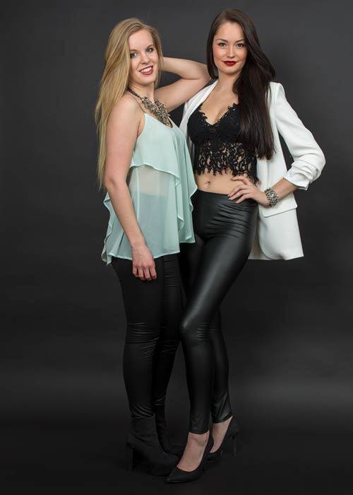 Doppelportrait zwei Freundinnen vor schwarzem Hintergrund